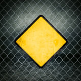 Sinal de aviso amarelo do Grunge na cerca de Chainlink de mercadorias industriais foto de stock