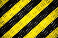 Sinal de aviso amarelo e listras pretas pintadas sobre a placa de aço do verificador ou a placa do diamante no assoalho como o fu imagem de stock
