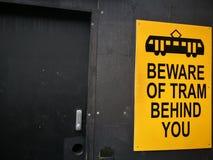 Sinal de aviso amarelo para o bonde Beware of atrás de você fotografia de stock royalty free