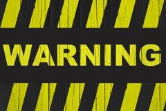 Sinal de aviso com as listras amarelas e pretas pintadas sobre madeira rachada imagens de stock