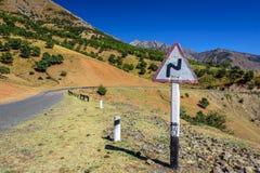 Sinal de aviso curvado da estrada no lado da estrada serpentina no fundo das montanhas cobertas com as árvores Foto de Stock