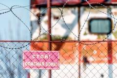 Sinal de aviso da zona de perigo da parada em trilhos da rede do metal com barbwire no por do sol foto de stock