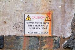 Sinal de aviso na parede do porto Fotografia de Stock Royalty Free