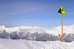 Sinal de aviso no precipício do inverno da neve da estância de esqui imagens de stock