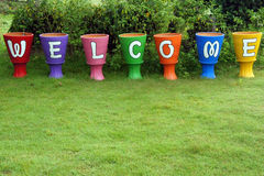 Sinal de boas-vindas, no potenciômetro de flor Imagens de Stock Royalty Free