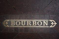 Sinal de Bourbon Street encaixado no passeio no bairro francês de Nova Orleães imagem de stock