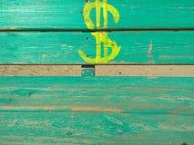 sinal de dólar tirado na pintura amarela em um banco de madeira verde foto de stock