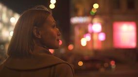Sinal de sinal de espera da mulher cruzar a estrada, apreciando a iluminação da cidade video estoque