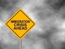 Sinal de estrada amarelo com a mensagem da crise da imigração adiante isolada em um fundo cinzento do céu Sinal de aviso amarelo  Fotografia de Stock Royalty Free