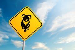 Sinal de estrada australiano dos animais selvagens da coala com céu azul e nuvem para trás imagem de stock
