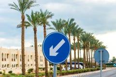 Sinal de estrada azul redondo com a seta de advert?ncia diagonal branca Quadro horizontal fotografia de stock