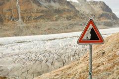 Sinal de estrada com aviso contra rochas de queda fotografia de stock