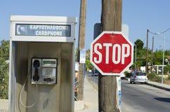 Sinal de estrada com sinal da parada e cabine de telefone em Grécia Imagens de Stock Royalty Free