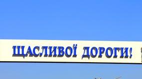 Sinal de estrada com palavras na estrada feliz ucraniana Foto de Stock