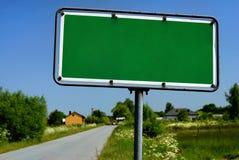Sinal de estrada com a vila no fundo Imagens de Stock Royalty Free