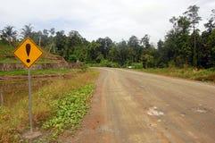 Sinal de estrada de advertência amarelo na estrada do cascalho fotos de stock