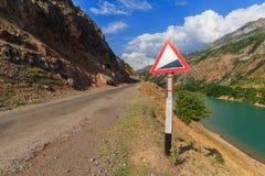 Sinal de estrada de advertência A paisagem de Usbequistão Montanhas ocidentais de Usbequistão, Tien Shan fotografia de stock royalty free