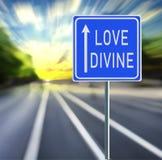 Sinal de estrada divino do amor em um fundo rápido com por do sol imagem de stock