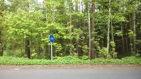 Sinal de estrada, estrada, árvores, folha, grama, vegetação densa, troncos de árvore, sinal redondo, árvores finas Fotos de Stock