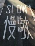 Sinal de estrada de marcado lento em uma pista de bicicleta fotos de stock