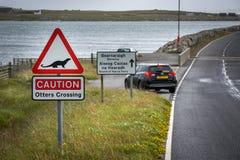 Sinal de estrada para as lontras que cruzam-se na ilha de Uist norte, Escócia fotos de stock