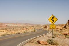 Sinal de estrada para curvas no deserto Fotos de Stock Royalty Free