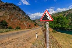Sinal de estrada Rochas de queda Montanhas ocidentais de Usbequistão, Tien Shan fotos de stock