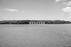 Sinal de Kuantan no rio em Malásia Água do rio e costa verde no céu azul Férias de verão Descoberta e aventura foto de stock royalty free
