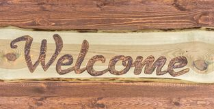 Sinal de madeira caseiro com a palavra inglesa para a boa vinda fotografia de stock royalty free
