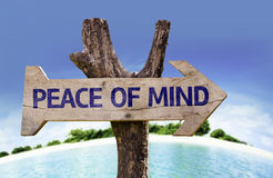 Sinal de madeira da paz de espírito com uma praia no fundo Fotos de Stock