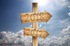 Sinal de madeira de 2017 e de 2018 dentro exatamente no fundo do céu azul Imagem de Stock Royalty Free