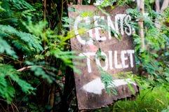 Sinal de madeira para o toalete dos senhores nos arbustos Imagem de Stock Royalty Free
