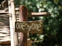 sinal de madeira que diz um por um foto de stock