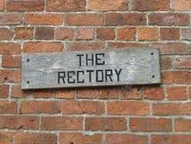 Sinal de madeira resistido velho da reitoria em uma parede de tijolo Fotografia de Stock Royalty Free