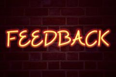 Sinal de néon do feedback no fundo da parede de tijolo Sinal fluorescente do tubo de néon no conceito do negócio da alvenaria par Imagem de Stock Royalty Free