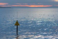 Sinal de naufrágio da lama do perigo na frente do mar e do por do sol Imagens de Stock Royalty Free