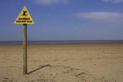 Sinal de naufrágio da lama do perigo, praia Inglaterra Reino Unido do ponto da areia Foto de Stock Royalty Free