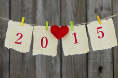 Sinal de papel antigo do ano 2015 com o coração vermelho que pendura da corda pela cerca de madeira Fotos de Stock Royalty Free