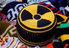 Sinal de perigo da radiação nuclear no chapéu feito malha Imagens de Stock