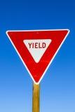 Sinal de rendimento na estrada com azul Imagem de Stock Royalty Free