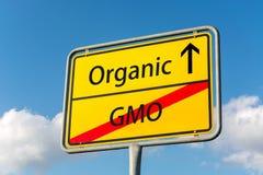 Sinal de rua amarelo com adiante GMO saindo orgânico atrás de u próximo Fotos de Stock Royalty Free