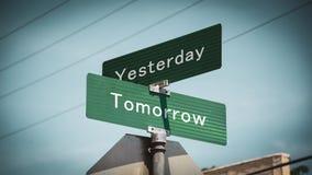 Sinal de rua ao amanhã contra ontem fotografia de stock