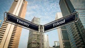 Sinal de rua ao amigo contra o inimigo fotos de stock