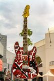 Sinal de rua colorido da cidade de uma guitarra elétrica vermelha foto de stock