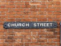 Sinal de rua da igreja unido à parede de tijolo fotografia de stock royalty free