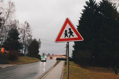 Sinal de rua do triângulo com a cidade europeia pequena das crianças Foto de Stock