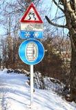 Sinal de rua e uma indicação da estrada escorregadiço e da neve chai fotografia de stock royalty free