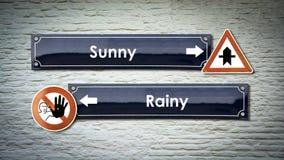 Sinal de rua ensolarado contra chuvoso foto de stock