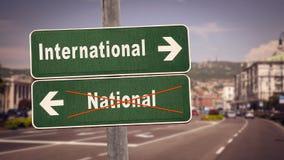 Sinal de rua a internacional contra o nacional fotografia de stock royalty free