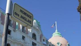 Sinal de rua de Promenade des Anglais, bandeira francesa que acena sobre a construção em agradável filme